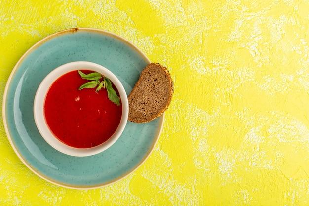 노란색 테이블에 어두운 빵 덩어리, 수프 음식 식사 저녁 식사와 상위 뷰 맛있는 토마토 수프