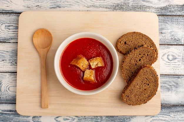 Vista dall'alto deliziosa zuppa di pomodoro con pagnotte di pane scuro sul tavolo grigio, cena di pasto di zuppa