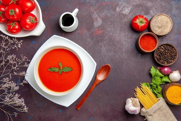 Вид сверху вкусный томатный суп со свежими помидорами и приправами на темном фоне блюдо соусом томатный суп
