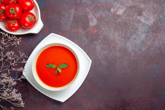 Top view delicious tomato soup with fresh tomatoes on dark background dish sauce tomato color meal soup