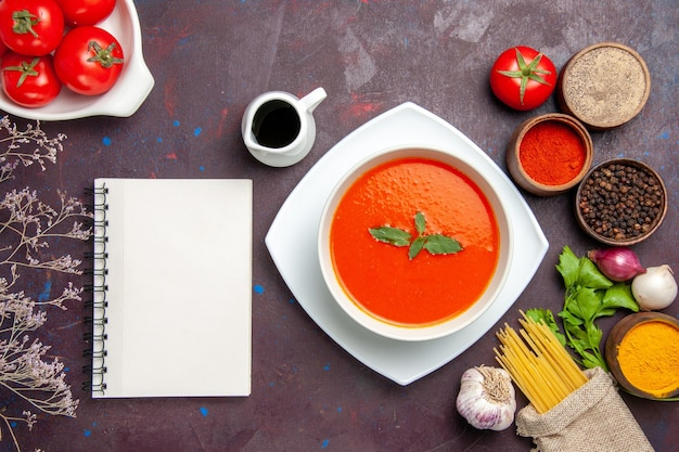 Top view delicious tomato soup with fresh tomatoes and seasonings on the dark background dish meal sauce tomato color soup