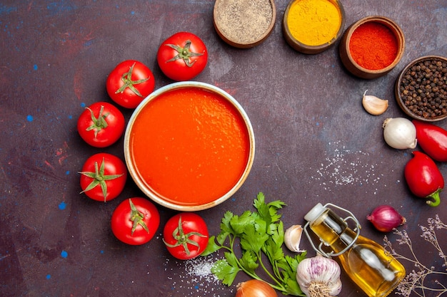 Top view delicious tomato soup with fresh tomatoes and seasonings on dark background tomatoes dish dinner soup sauce meal