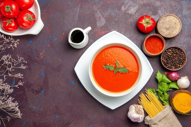 Top view delicious tomato soup with fresh tomatoes and seasonings on dark desk dish meal sauce tomato color soup