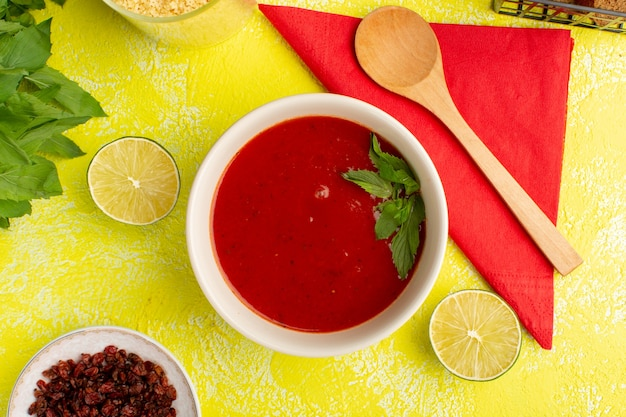Vista dall'alto deliziosa zuppa di pomodoro con verdure e limone sul tavolo giallo, verdura cena pasto zuppa