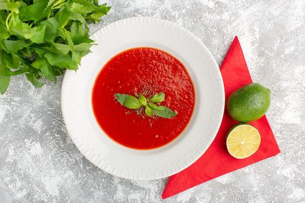 Vista dall'alto deliziosa zuppa di pomodoro con limone e verdure sulla tavola grigia, verdura cena pasto zuppa