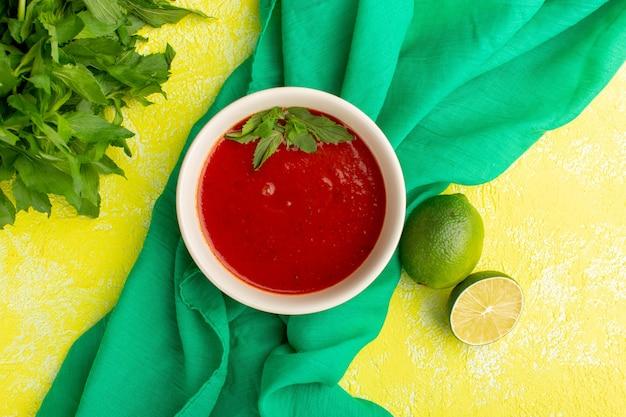 Vista dall'alto deliziosa zuppa di pomodoro con limone e verdure sul tavolo giallo, cena di pasto di zuppa