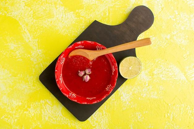 トップビュー黄色のテーブルにレモンとおいしいトマトスープ、スープミール野菜料理