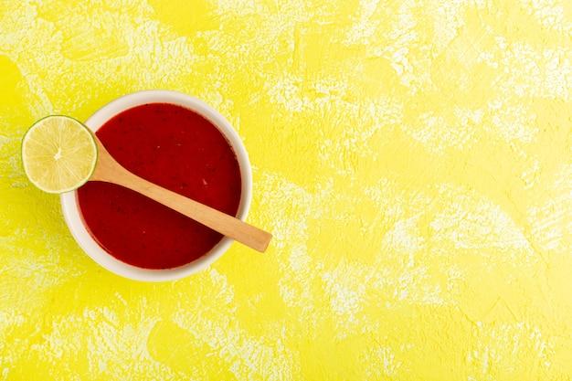 Vista dall'alto deliziosa zuppa di pomodoro con limone sulla tavola gialla, cena di pasto di zuppa