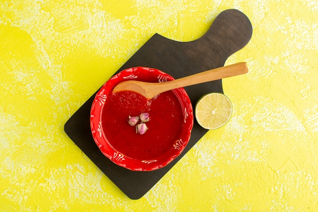 Top view delicious tomato soup with lemon on yellow table, soup meal vegetable food