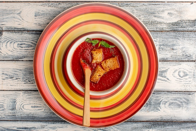 灰色の素朴なテーブルの上にラスクが入ったおいしいトマトスープ、スープミールディナー野菜の上面図