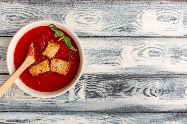 灰色のテーブルの上にラスクが入ったおいしいトマトスープの上面図、スープフードミールディナー