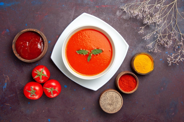 Top view delicious tomato soup with seasonings on dark background dish sauce tomato color meal soup