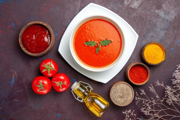 Top view delicious tomato soup with seasonings on the dark background dish sauce tomato color meal soup