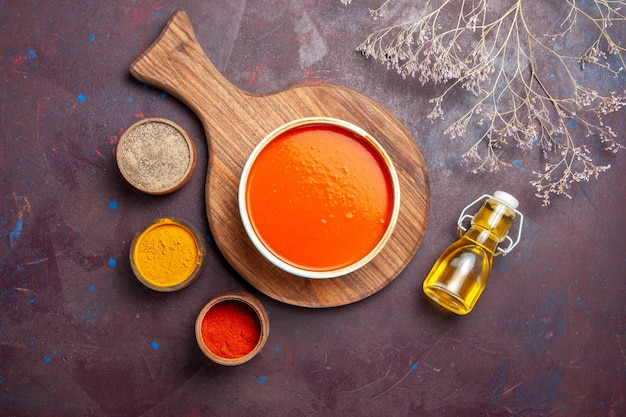 Top view delicious tomato soup with seasonings on dark background soup tomato dish meal sauce