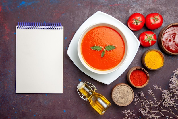 Top view delicious tomato soup with seasonings on dark floor dish sauce tomato color meal soup