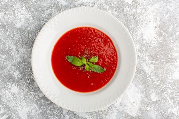 Вид сверху вкусный томатный суп с приправами на сером столе, суп, ужин, овощ