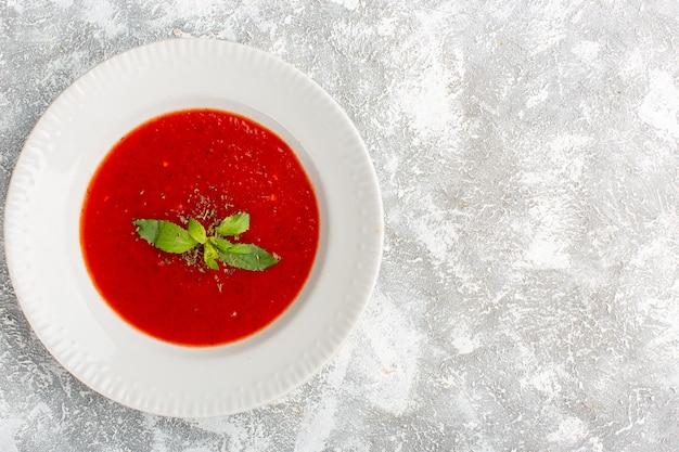 灰色のテーブルに調味料を入れたトップビューのおいしいトマトスープ、スープミールディナー
