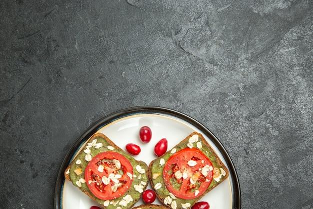 어두운 회색 배경에 접시 안에 아보카도 파스타와 토마토와 상위 뷰 맛있는 유용한 샌드위치 버거 샌드위치 빵 롤빵 스낵