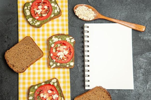Vista dall'alto deliziosi panini utili con pasta di avocado e pomodori su sfondo grigio hamburger panino pane panino spuntino