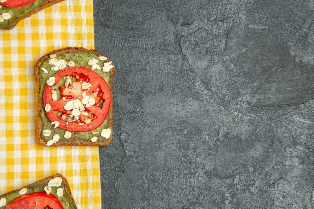 Top view delicious useful sandwiches with avocado pasta and tomatoes on grey background burger sandwich bread bun snack