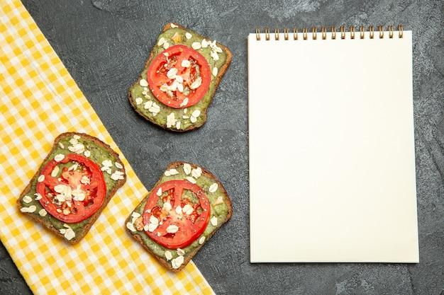 Vista dall'alto deliziosi panini utili con pasta di avocado e pomodori sullo spuntino del panino del pane dell'hamburger del panino della scrivania grigia