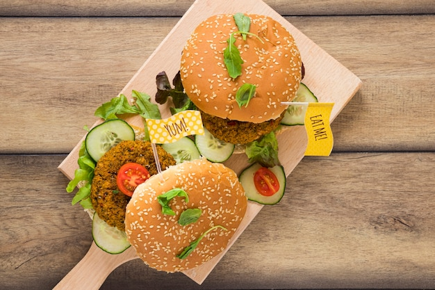 Top view delicious vegan burgers on wooden board