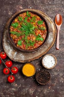 Вид сверху вкусной овощной еды, нарезанной со свежими овощами и приправами на темной поверхности еда ужин соус суп