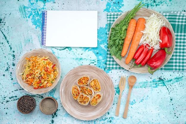 Vista dall'alto di deliziosi involtini di verdure affettati insieme a blocco note di insalata fresca e verdure sulla scrivania blu brillante, rotolo di insalata di farina di cibo vegetale