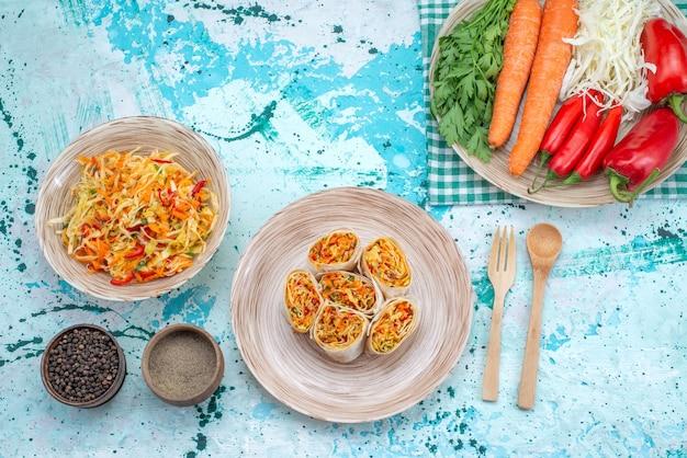 Vista dall'alto di deliziosi involtini di verdure affettati insieme a insalata fresca e verdure sulla scrivania blu brillante, rotolo di insalata di farina di cibo vegetale