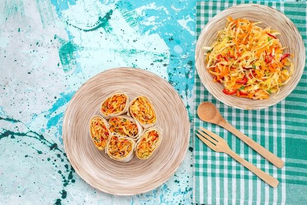 Vista dall'alto di deliziosi involtini di verdure affettati insieme a insalata di verdure fresche sulla scrivania blu brillante, rotolo di insalata di farina di cibo vegetale