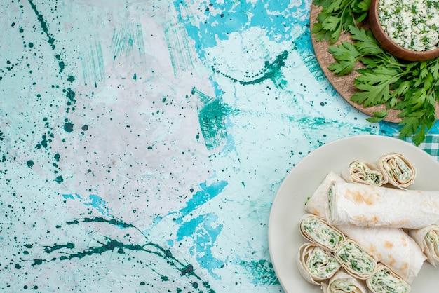 Vista dall'alto di deliziosi involtini di verdure intere e affettate con verdure e insalata sulla scrivania blu brillante, spuntino vegetale
