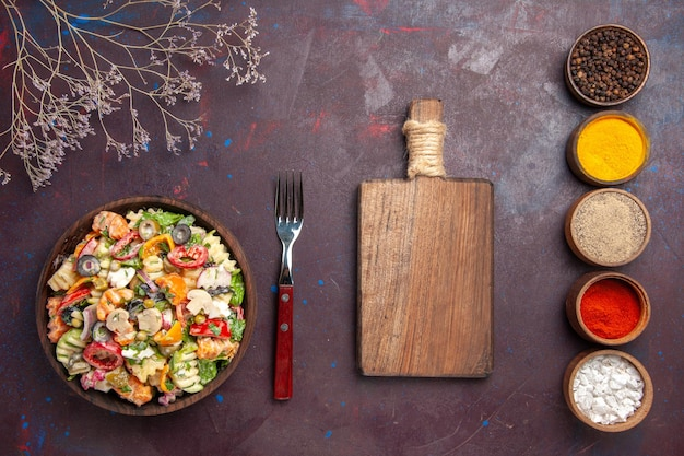Top view delicious vegetable salad with different seasonings on dark background health diet vegetables salad lunch