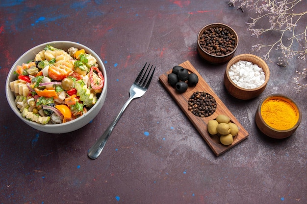Top view delicious vegetable salad with different seasonings on a dark background health salad meal diet