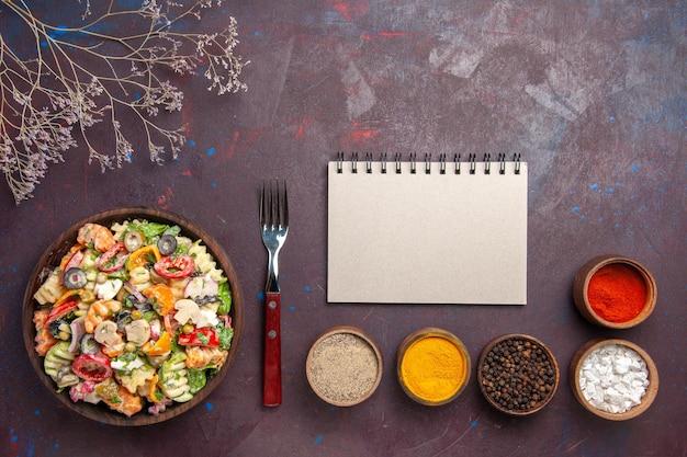 Вид сверху вкусный овощной салат с разными приправами на темном фоне здоровая диета овощной салат обед