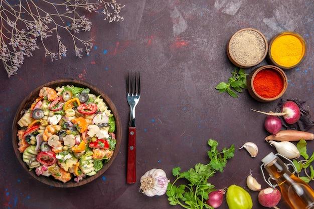 Вид сверху вкусный овощной салат с разными приправами на темном фоне здоровый овощной диетический обед салат