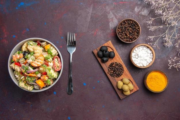 暗い背景の健康サラダ食事ダイエットにさまざまな調味料を使ったトップビューのおいしい野菜サラダ