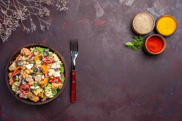 暗い背景の健康野菜ダイエットランチサラダにさまざまな調味料を使ったトップビューのおいしい野菜サラダ