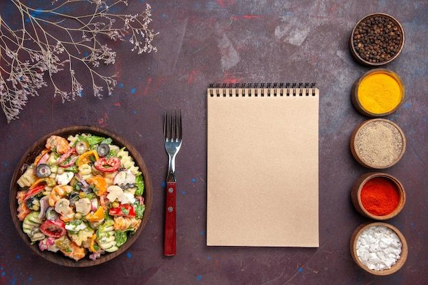 Вид сверху вкусный овощной салат с разными приправами на темном столе здоровый диетический овощной салат обед
