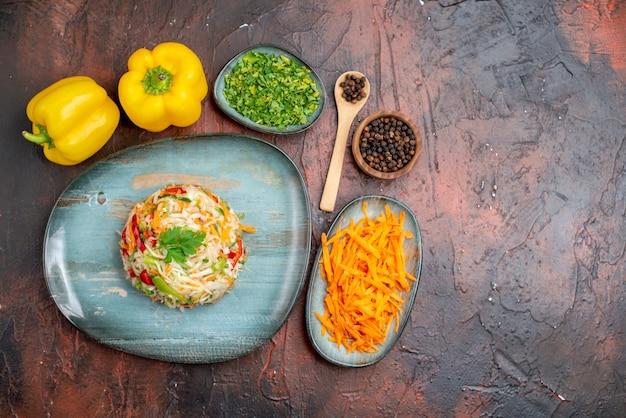 暗い背景色の緑とニンジンのトップビューおいしい野菜サラダ熟した食品の食事健康的な生活の写真