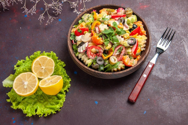 Вид сверху вкусный овощной салат с дольками лимона и зеленым салатом на темном фоне салатная еда здоровая диета