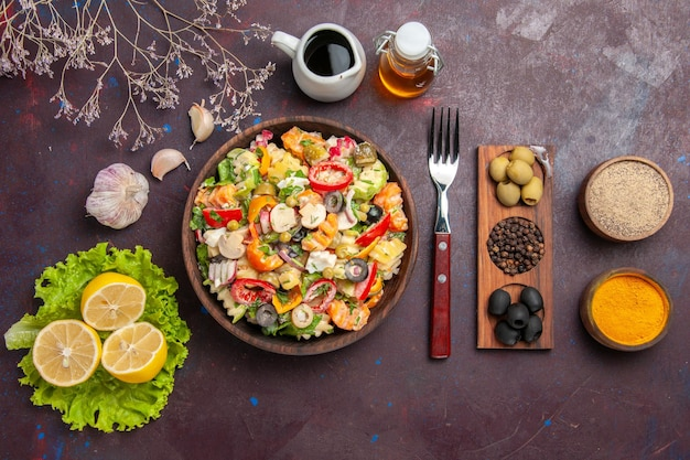 Top view delicious vegetable salad with lemon slices on dark background meal diet salad health food