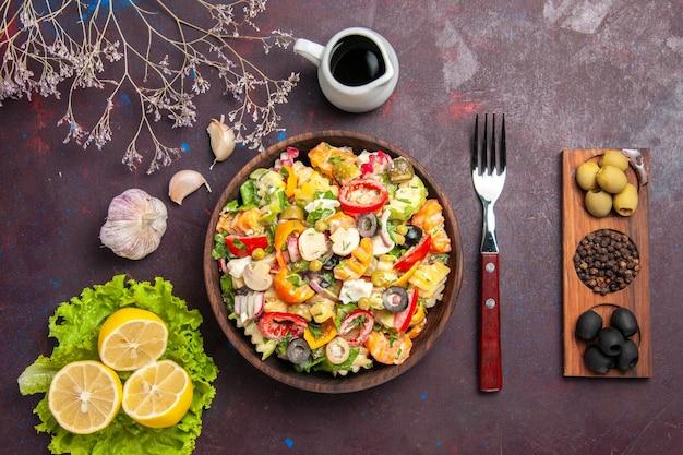 Vista dall'alto deliziosa insalata di verdure con fette di limone e insalata verde su sfondo scuro pasto dieta insalata salute