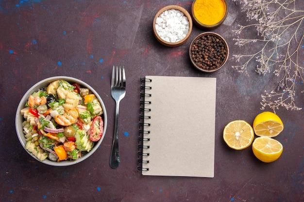 暗い背景の健康サラダ食事ダイエットに調味料と新鮮なレモンスライスとトップビューおいしい野菜サラダ