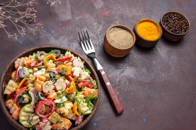 Top view delicious vegetable salad with seasonings on a dark background health diet salad vegetable lunch