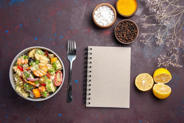 Vista dall'alto deliziosa insalata di verdure con condimenti e fette di limone fresco su sfondo scuro dieta di insalata salutare