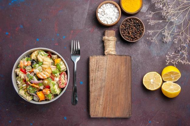 Vista dall'alto deliziosa insalata di verdure con condimenti e fette di limone su dieta di insalata di salute da scrivania scura dark