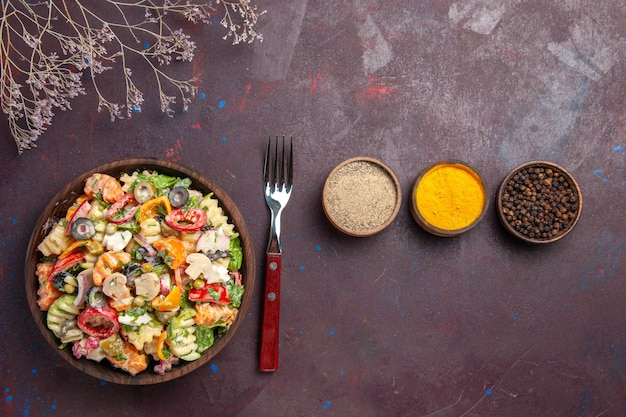 Вид сверху вкусный овощной салат с приправами на темном фоне здоровый диетический салат овощной обед