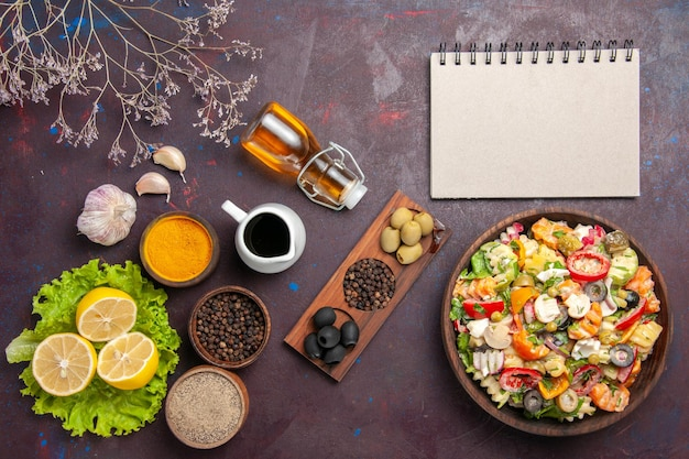 Top view delicious vegetable salad with sliced tomatoes olives and mushrooms on the dark background meal diet health food salad