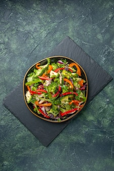 Top view of delicious vegetable salad with various ingredients on black cutting board on dark background