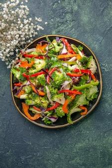 Vista dall'alto di deliziosa insalata di verdure con vari ingredienti su tagliere nero